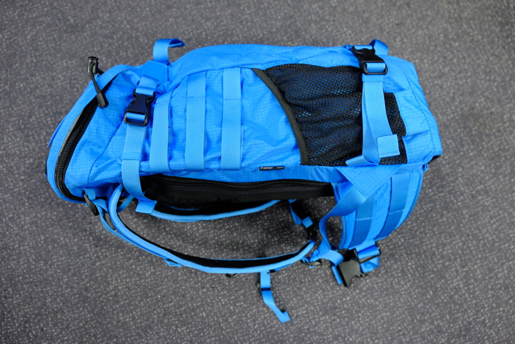 The side of the pack has two compression straps, a webbed pocket and molle attachment straps. Usually I store my tripod on one of the two sides