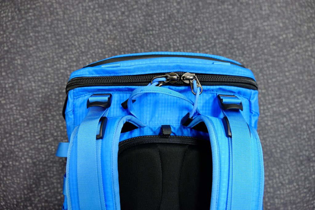 The zipper of the top compartment is large and rugged. There are also straps to pull the pack towards your back and keep the weight towards your body